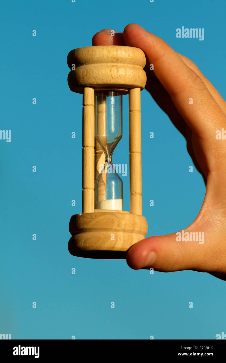 Sablier Hourglass a tenu jusqu'à un fond bleu ciel en soirée avec la lumière au coucher du soleil Banque D'Images