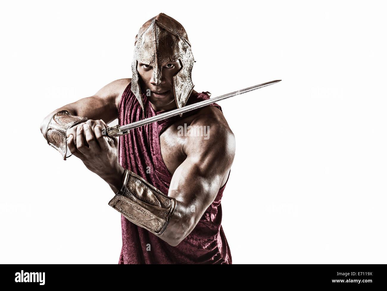 Studio portrait of muscular young man dressed comme gladiator avec casque et épée Photo Stock