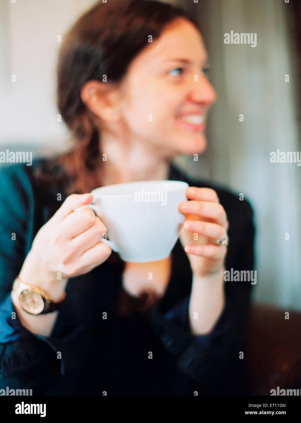 Une femme tenant un grand blanc chine tasse et à la recherche sur le côté en souriant. Photo Stock