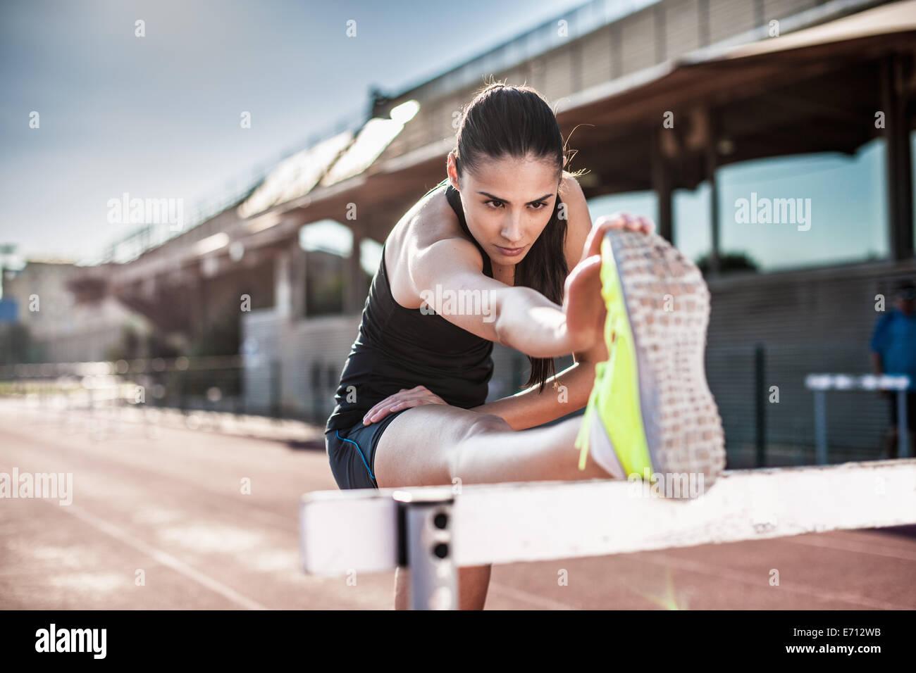 Jeune femme qui s'étend de la jambe sur obstacle Photo Stock