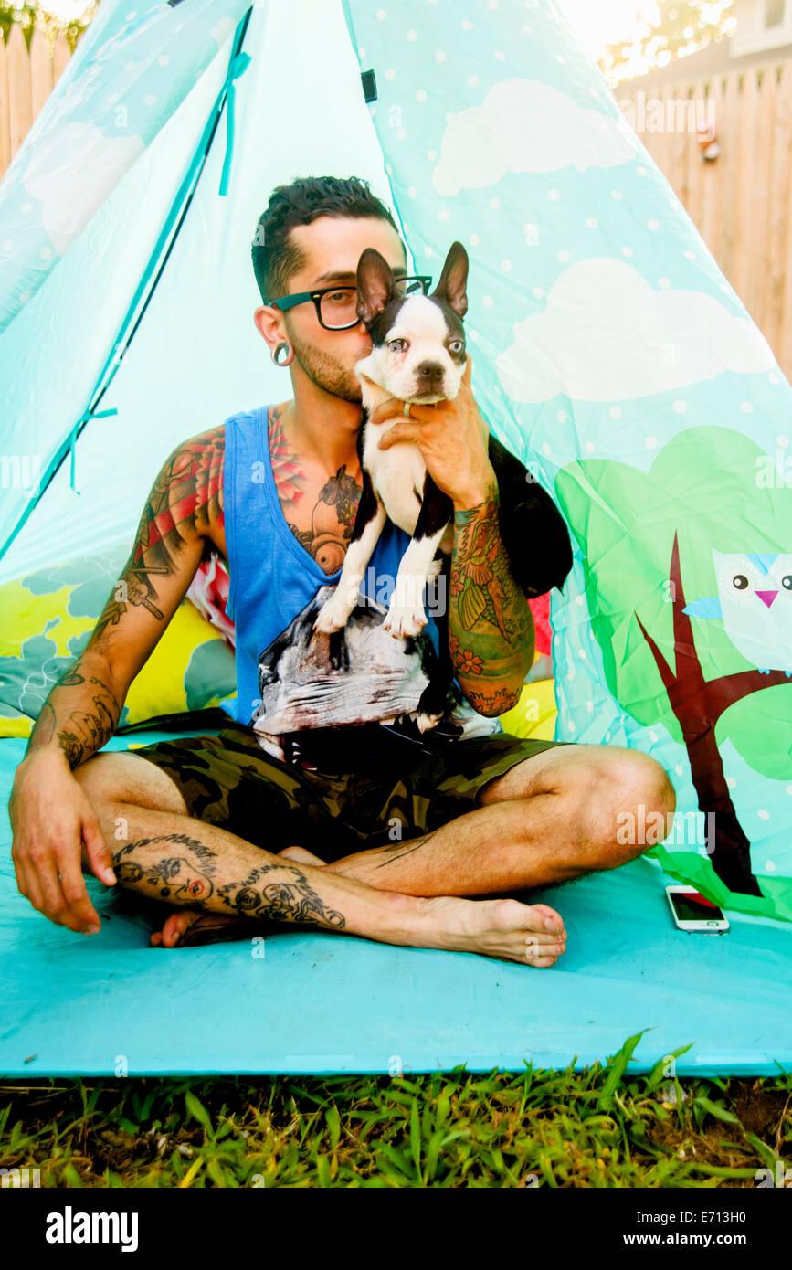 Portrait de funky man holding up son chien de compagnie Banque D'Images