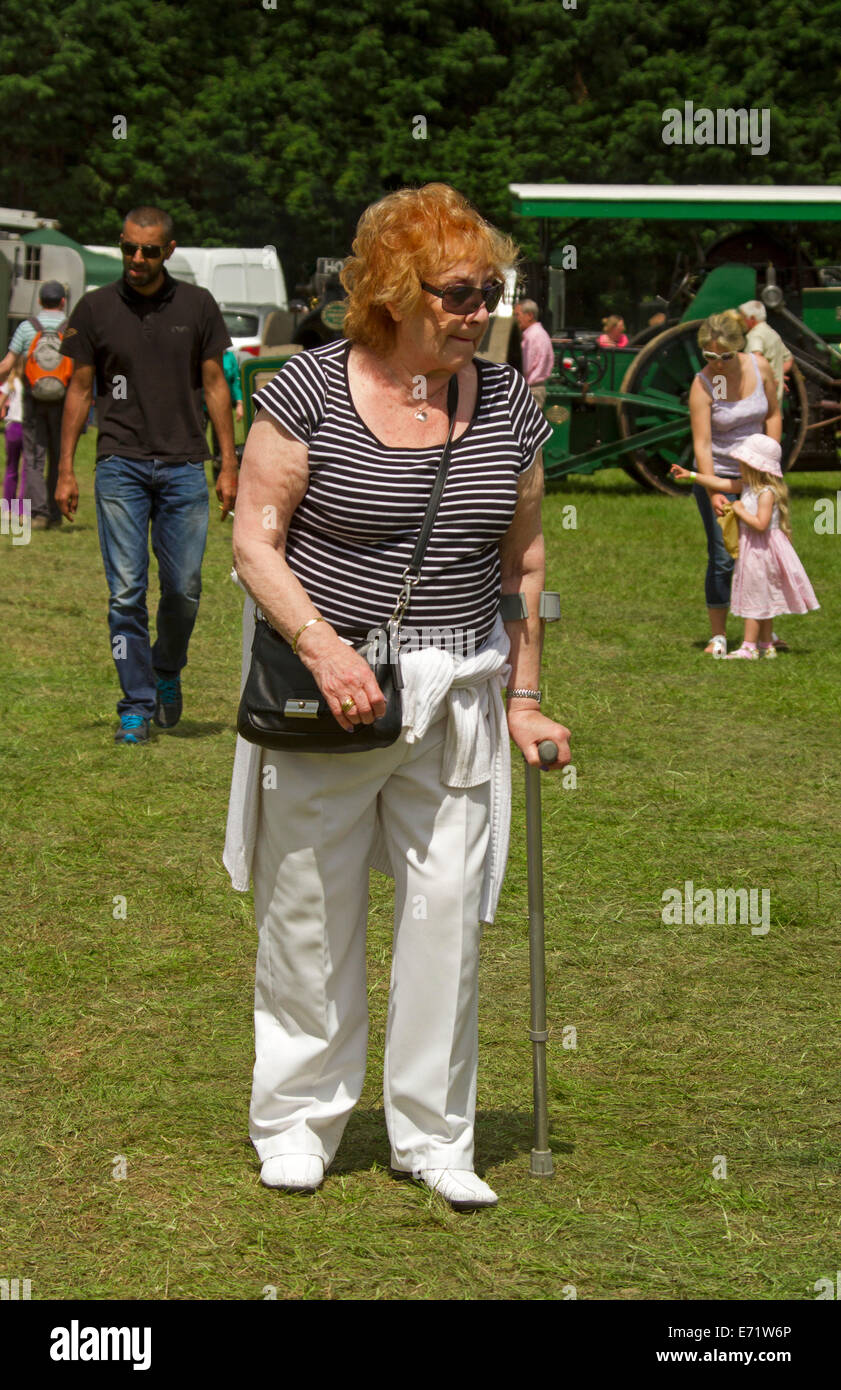 Vieille Femme aux cheveux rouges et portant des T-shirt à rayures et un pantalon blanc à marcher avec Photo Stock