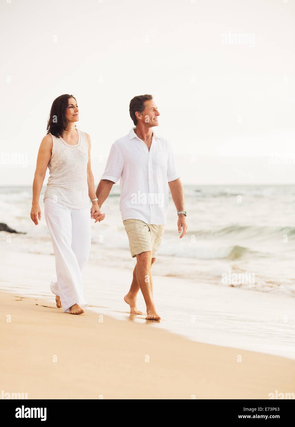 Mature couple de retraités profitant de coucher du soleil à pied sur la plage Photo Stock