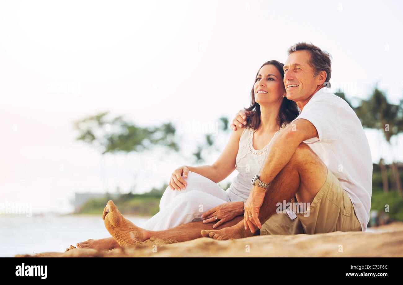 Happy Young Couple Enjoying Coucher du soleil sur la plage Photo Stock