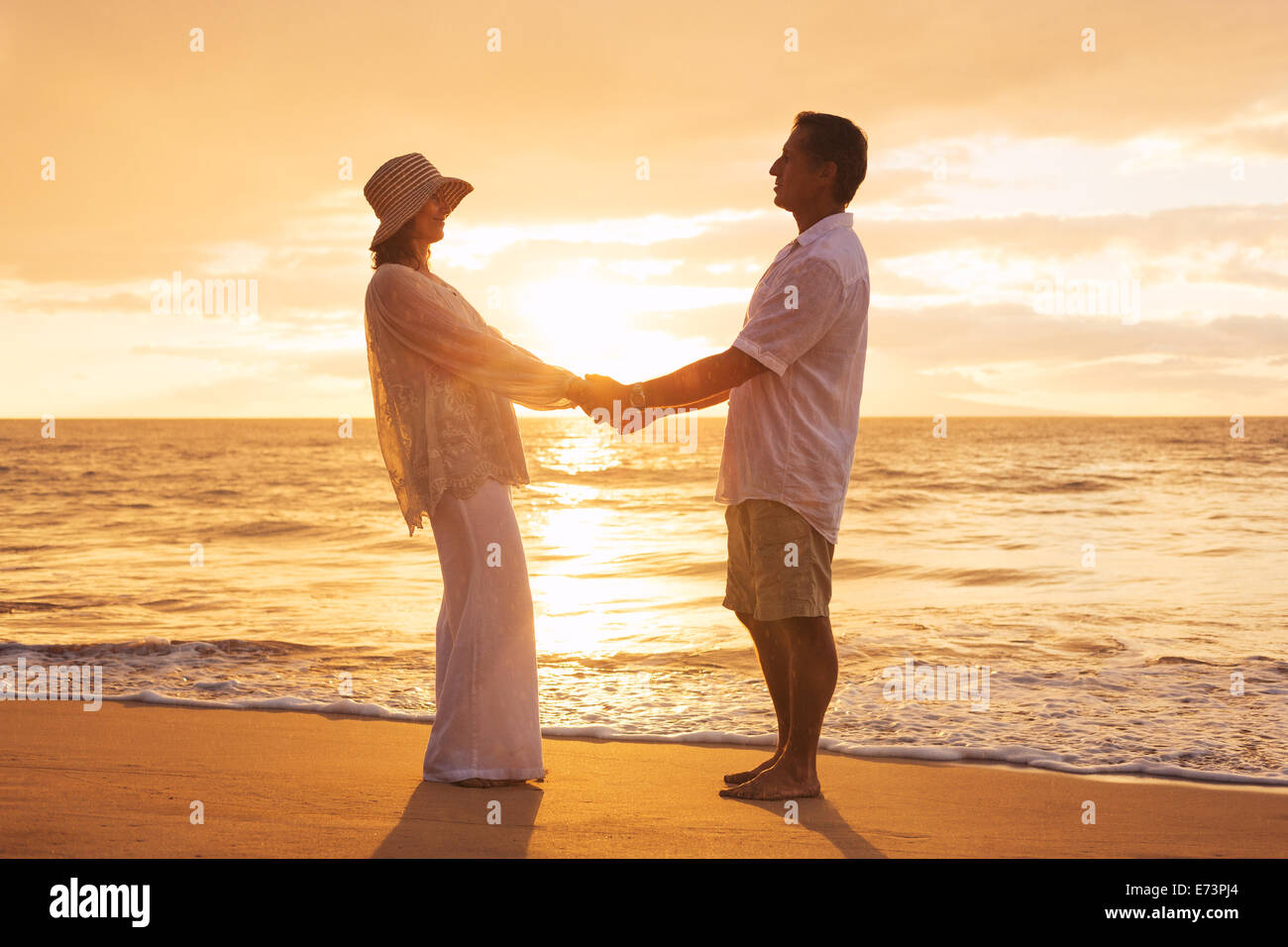 Mature Couple romantique au coucher du soleil sur la plage à Hawaii Photo Stock
