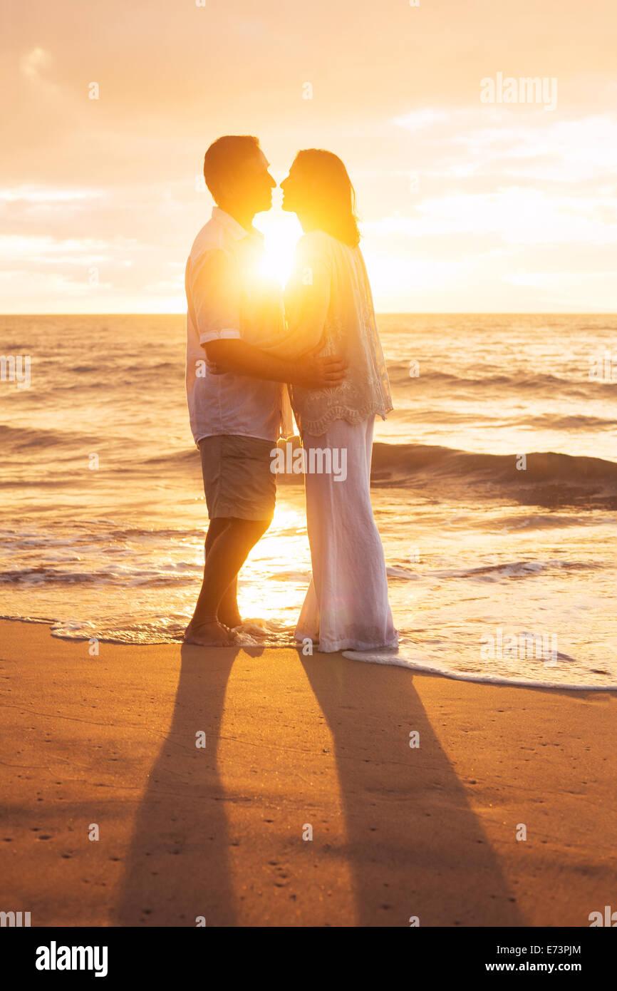 Mature Couple Kissing romantique au coucher du soleil sur la plage Photo Stock