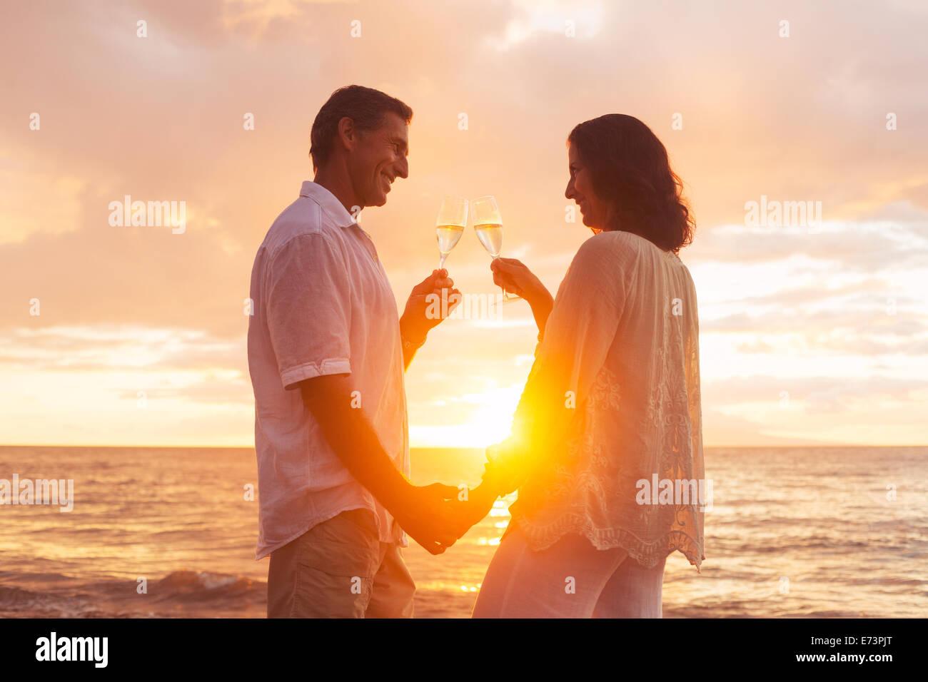 Happy Romantic Couple Enjoying verre de champagne au coucher du soleil sur la plage. La retraite de voyages vacances Photo Stock