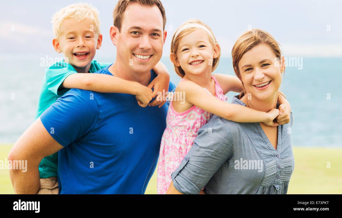 Portrait de famille heureuse à l'extérieur sur l'herbe Photo Stock