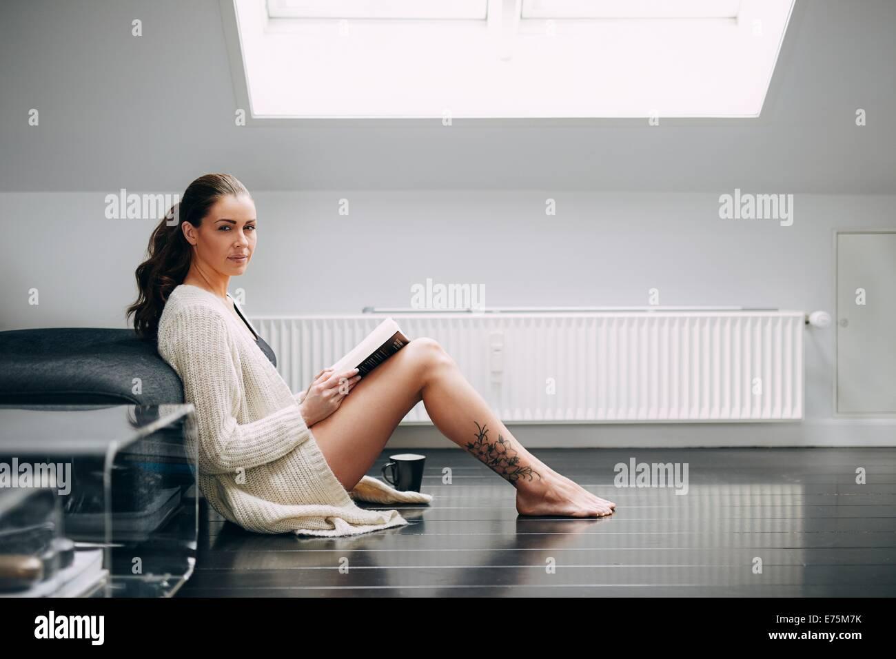 Belle brune femme lisant un livre d'un canapé. Joli modèle féminin assis sur le plancher avec un livre à la recherche Banque D'Images