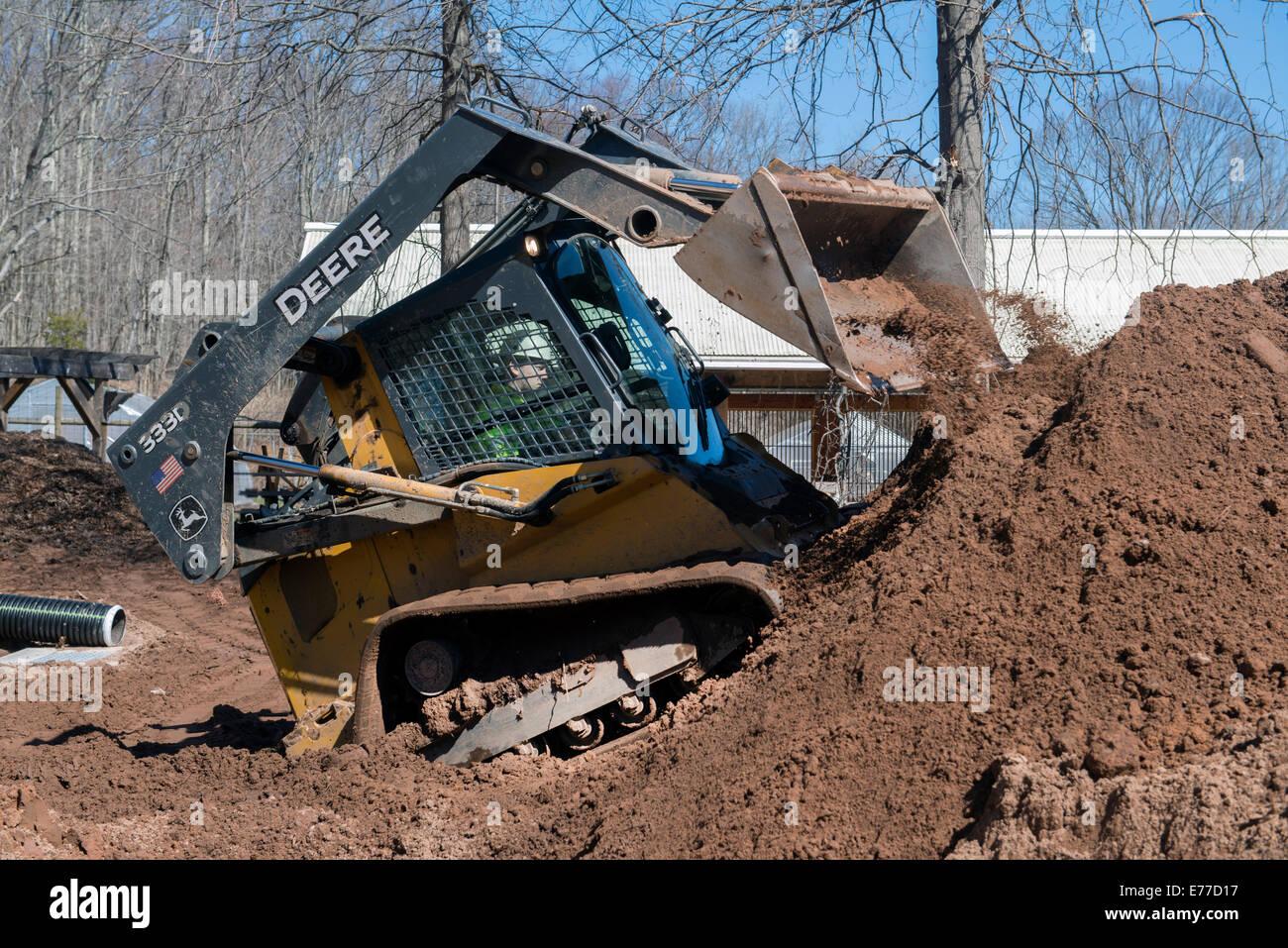 Deere chargeur Skid Steer se déplace de la saleté. Photo Stock