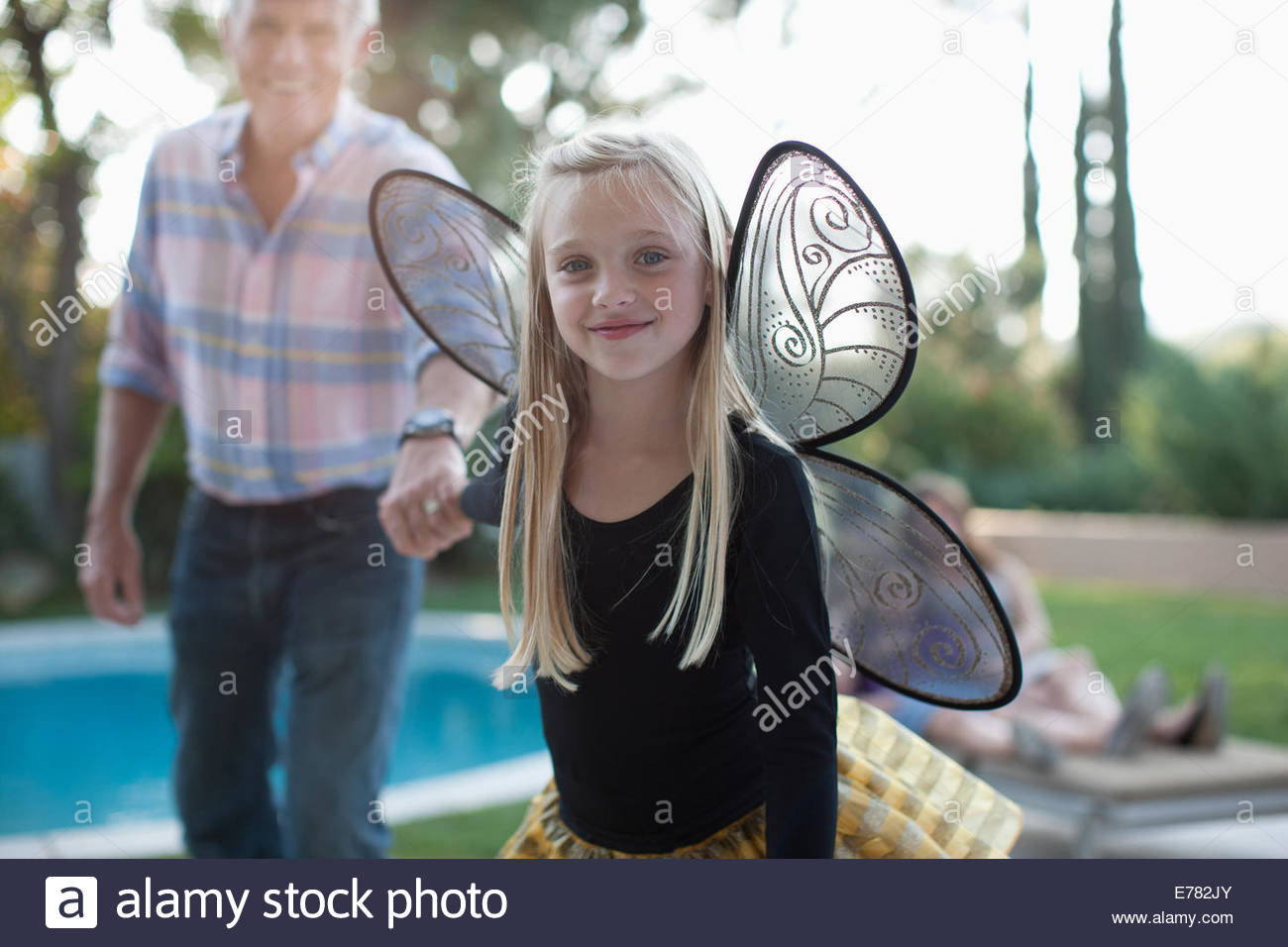 Girl in fairy wings tirant le long de grand-père Photo Stock