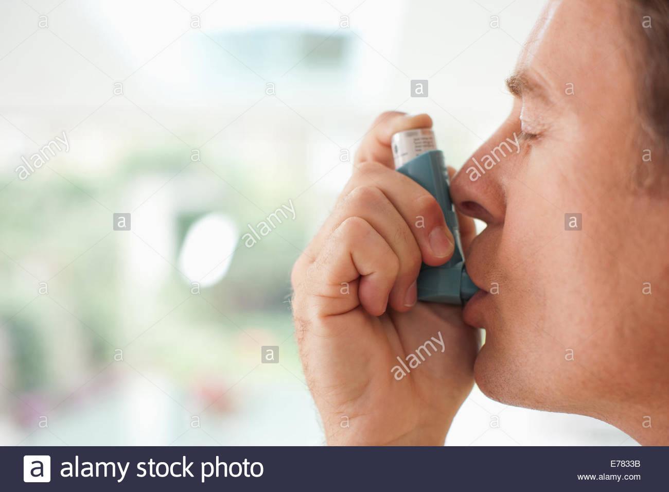 À propos de l'homme d'utiliser l'inhalateur d'asthme Photo Stock