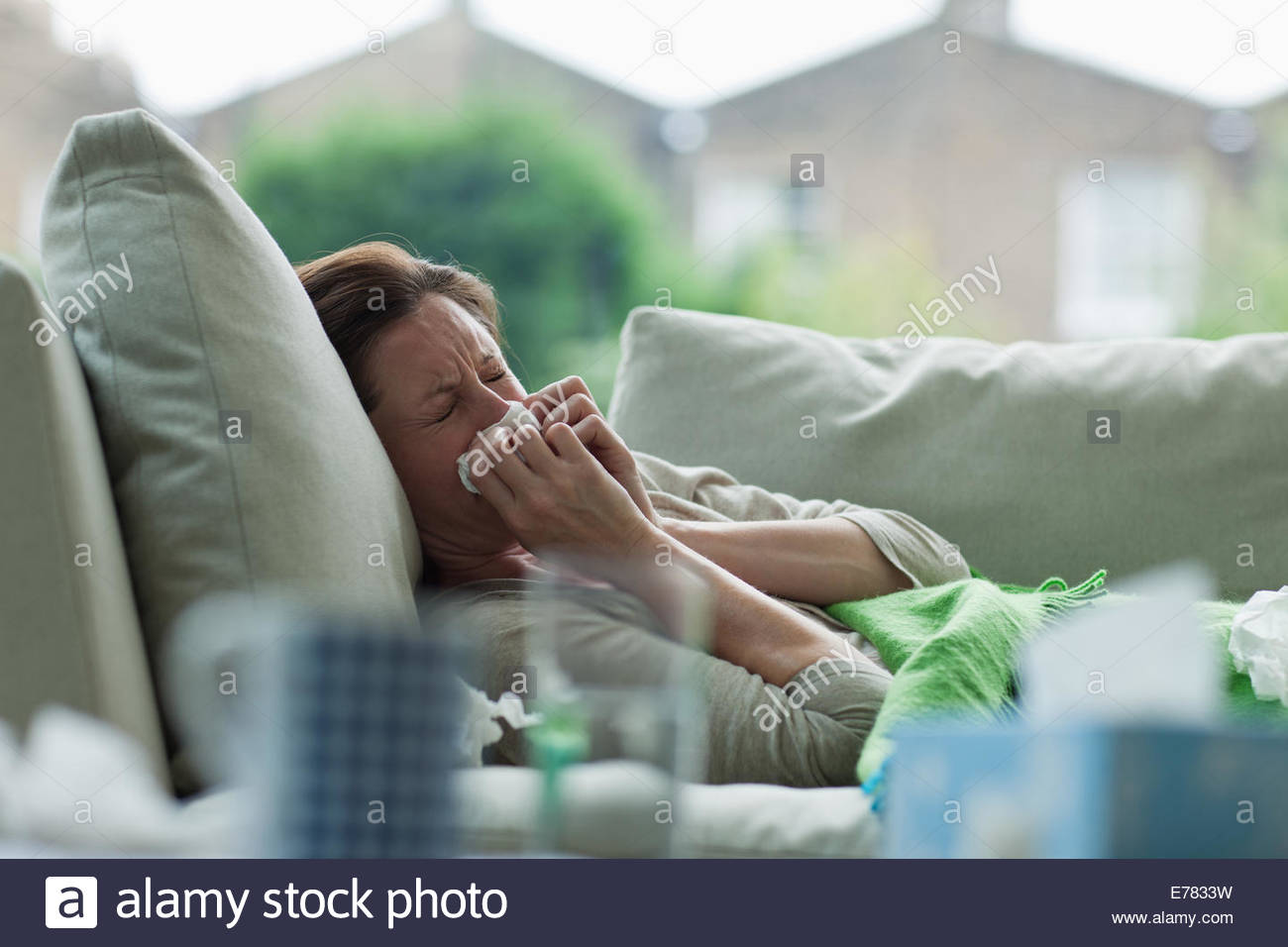 Femme malade portant sur canapé blowing nose Photo Stock
