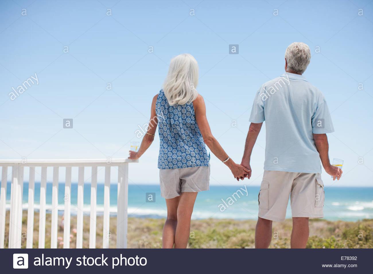 Senior couple holding hands on beach patio Photo Stock