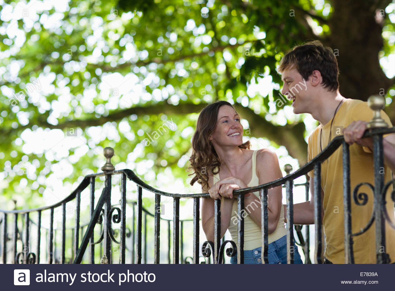 Smiling couple leaning on railing outdoors Photo Stock