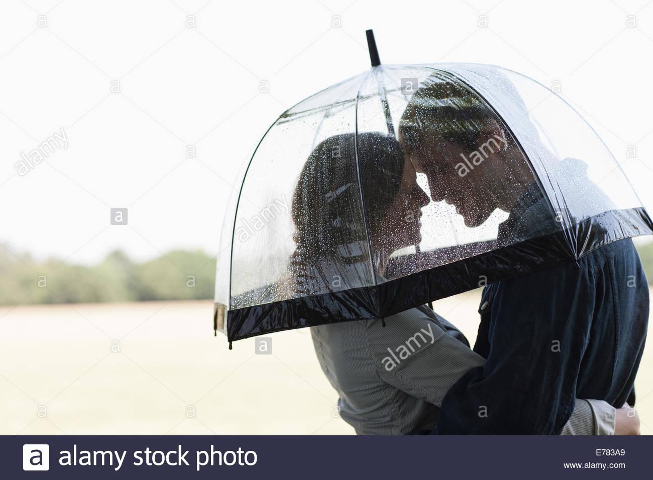Dans la pluie couple hugging sous égide Photo Stock