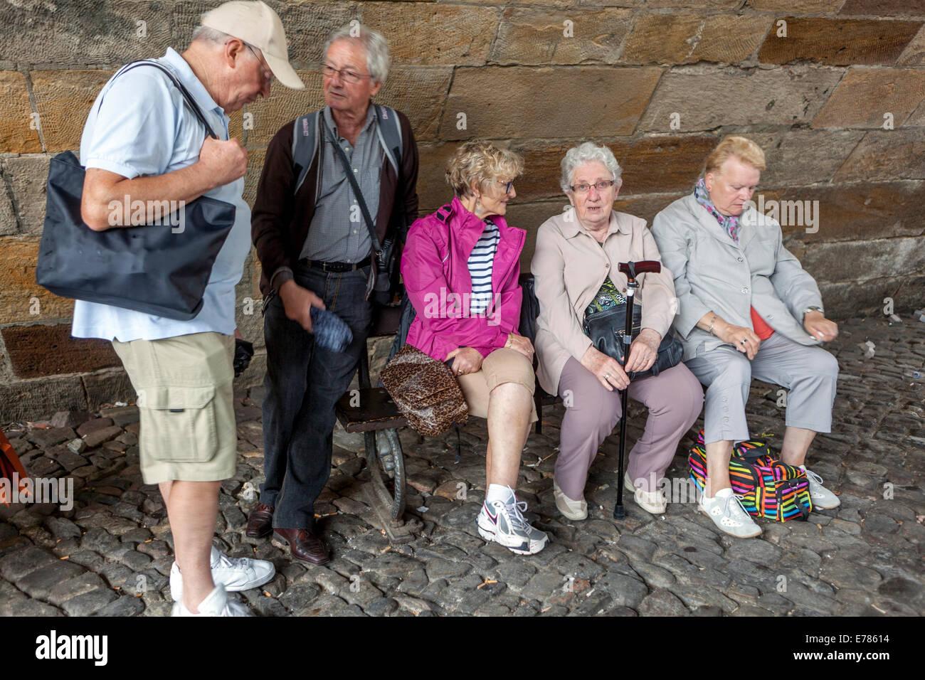 Personnes âgées touristes fatigués, relaxation, les retraités sur le banc sous le pont Charles, Photo Stock