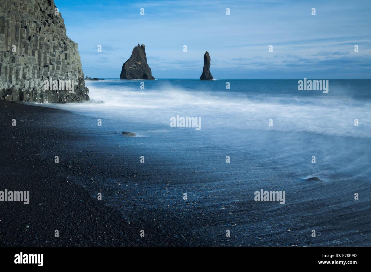 Les colonnes basaltiques de Reynisdrangar et la plage de sable noir de Reynisfjara qui jouit près du village Photo Stock