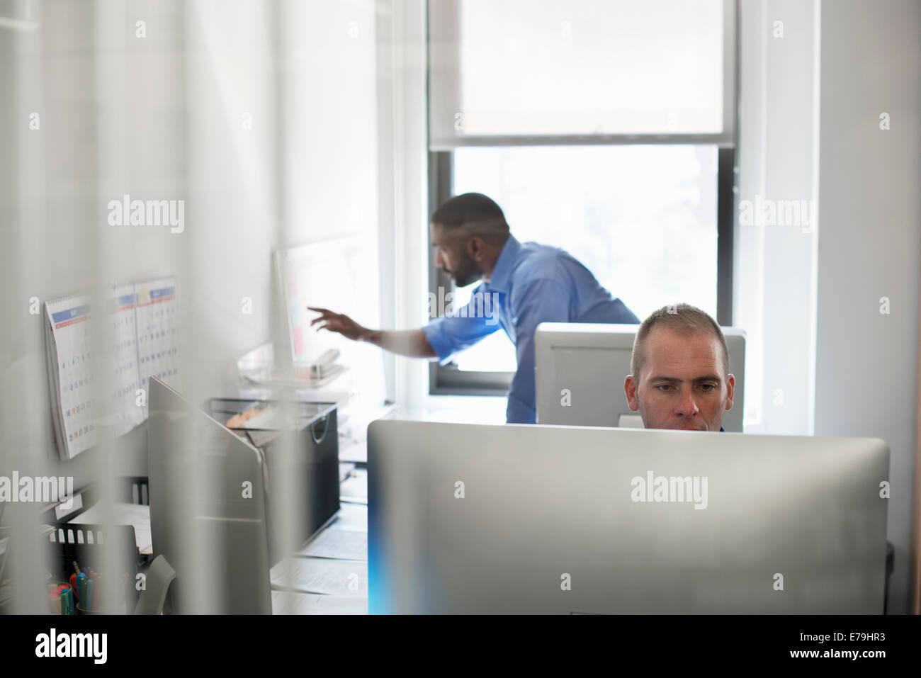 Un homme assis à un ordinateur, et l'un travaillant sur un tableau mural planner. Photo Stock