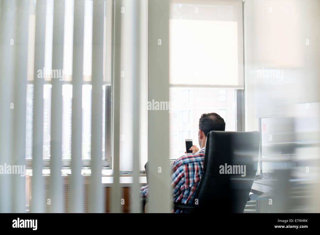 Un homme assis dans un grand fauteuil, se penchant en arrière et contrôler son téléphone intelligent. Banque D'Images