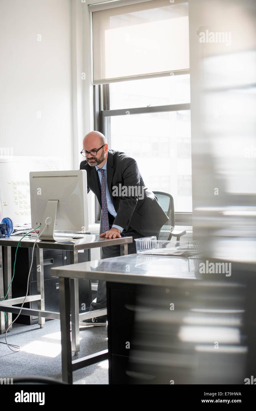 La vie de bureau. Un homme travaillant seul dans un bureau. Photo Stock