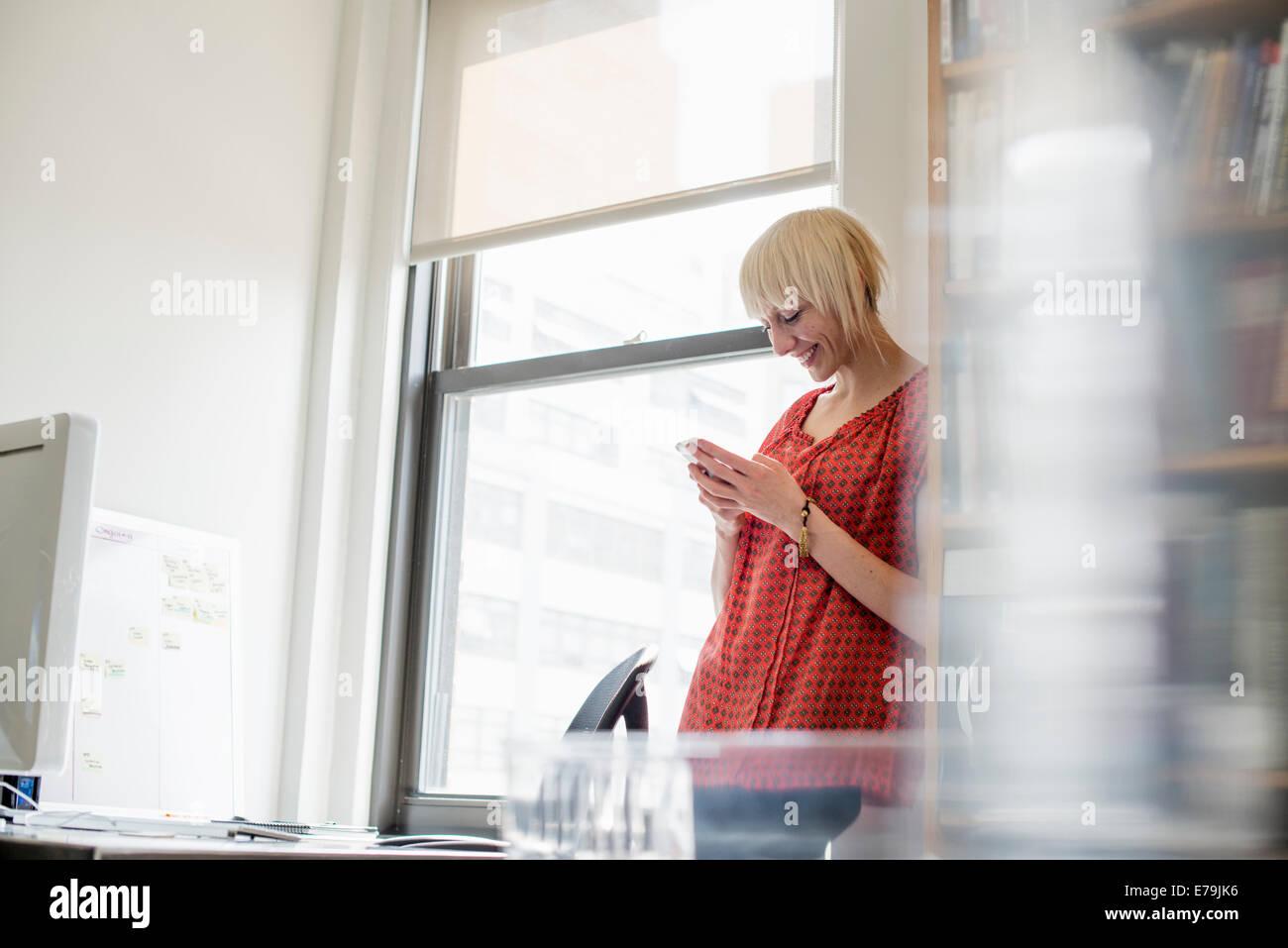 La vie de bureau. Une jeune femme contrôler son téléphone cellulaire. Photo Stock