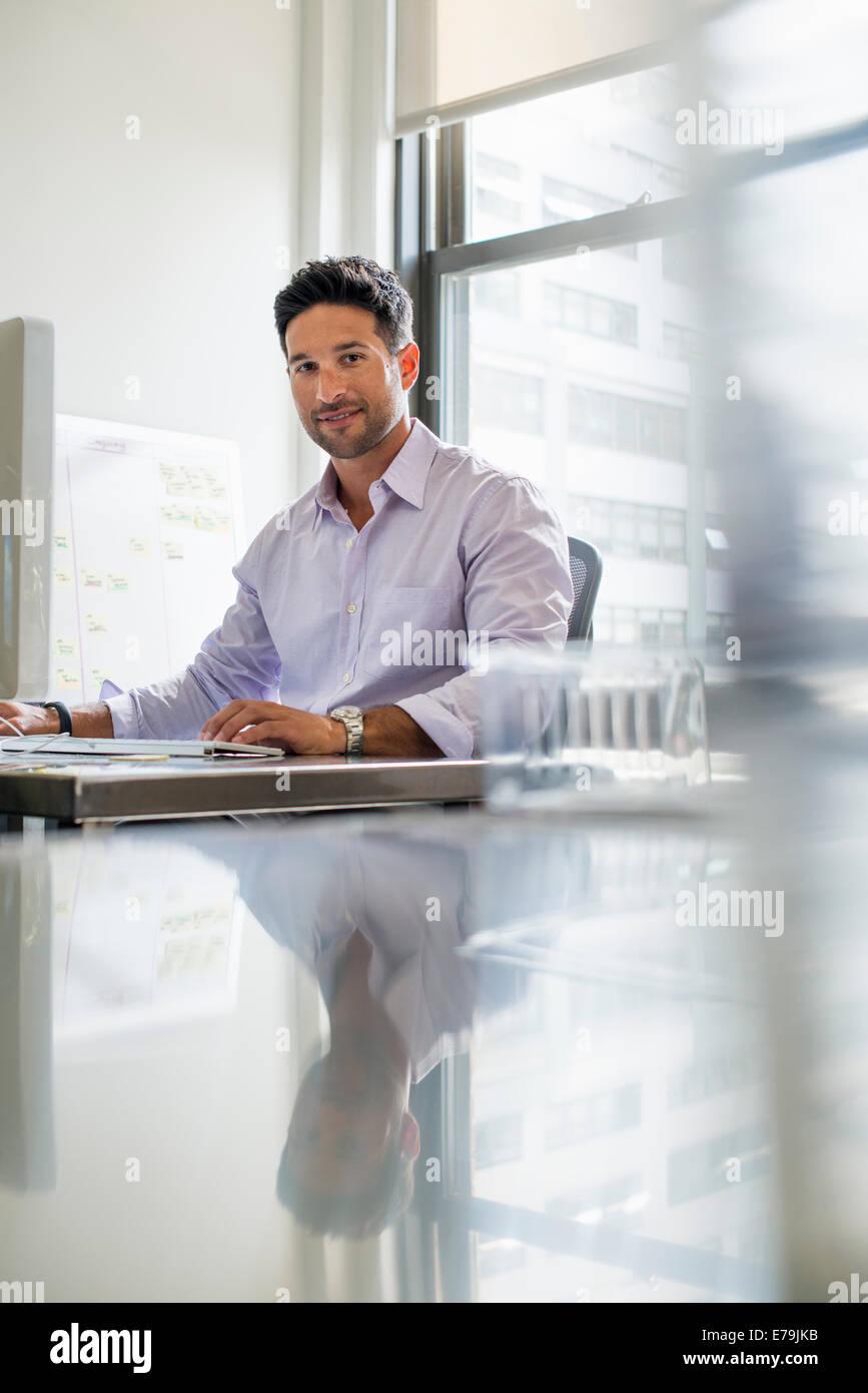 La vie de bureau. Un homme assis à son bureau. Photo Stock