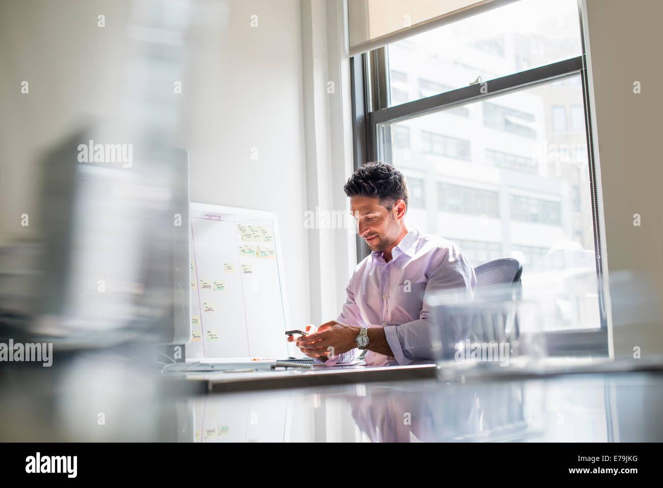 La vie de bureau. Un homme contrôler son téléphone dans un bureau. Photo Stock