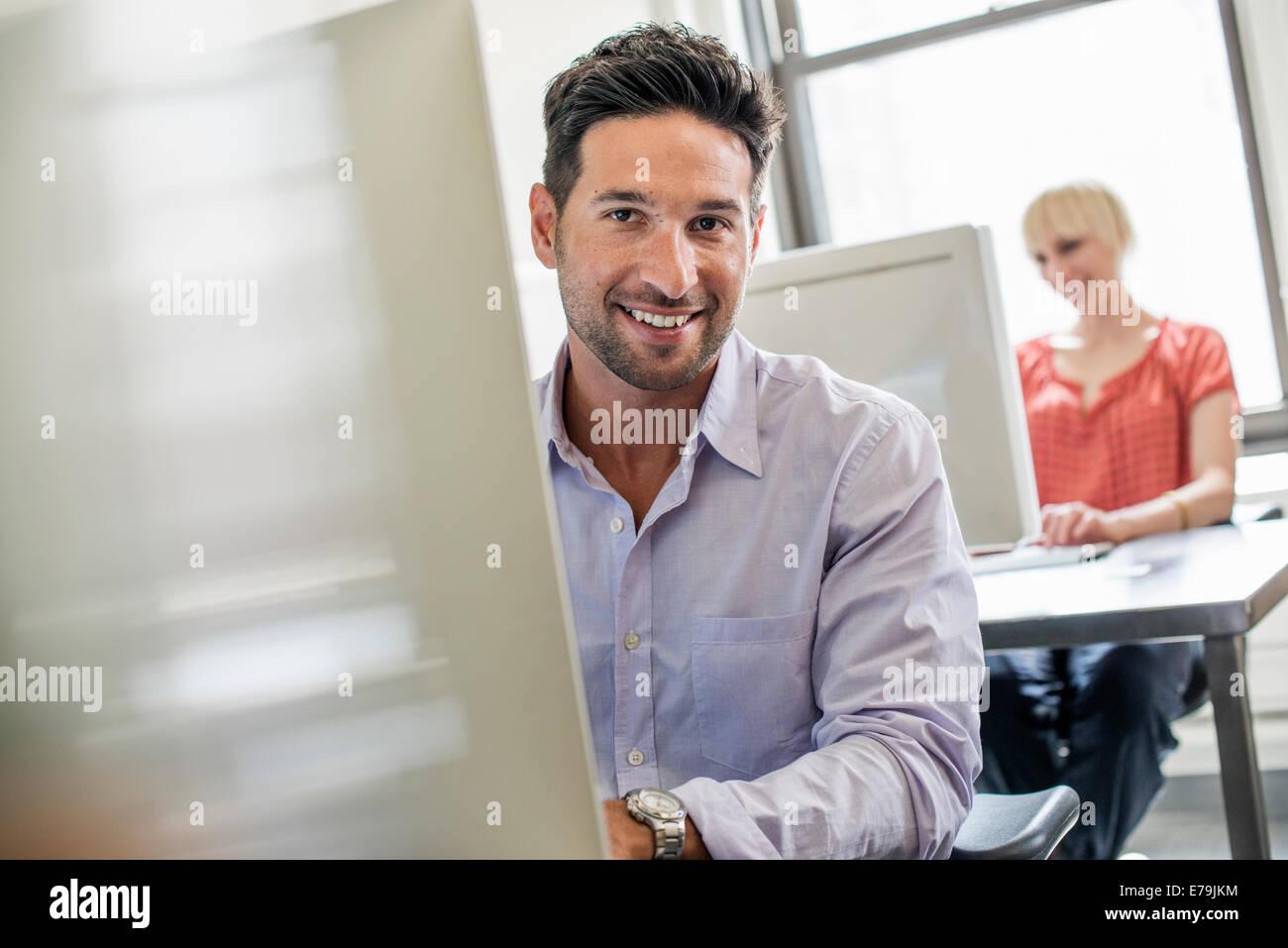 La vie de bureau. Deux personnes assis à un bureau à l'aide d'ordinateurs. Photo Stock