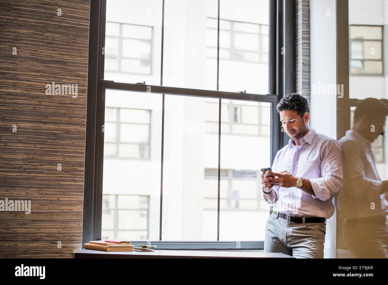 La vie de bureau. Un homme dans un bureau vérifie son téléphone intelligent. Photo Stock
