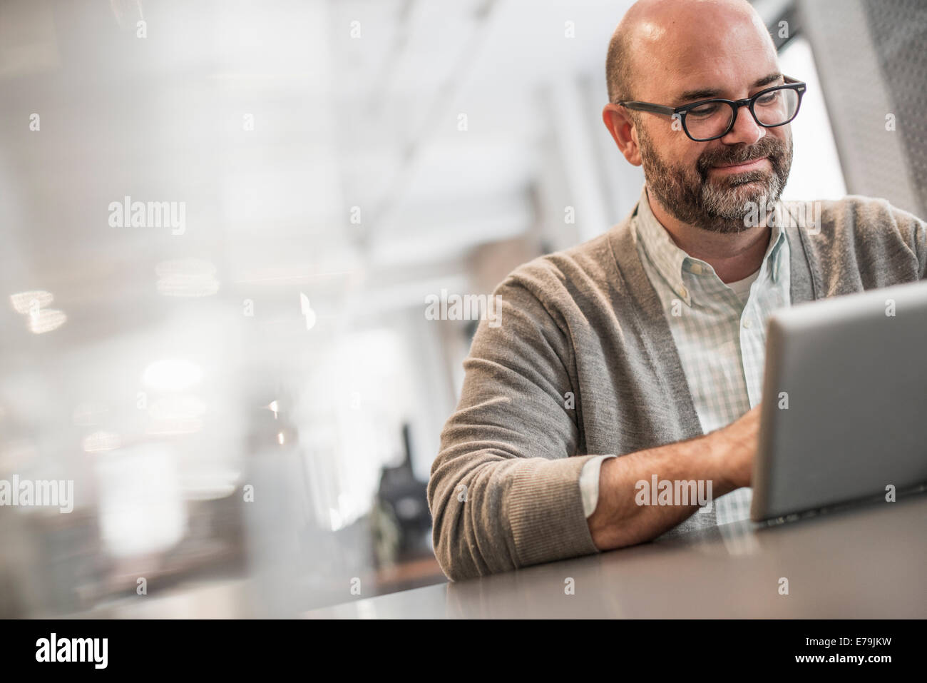 La vie de bureau. Un homme assis à une table, en train de travailler sur un ordinateur portable. Photo Stock
