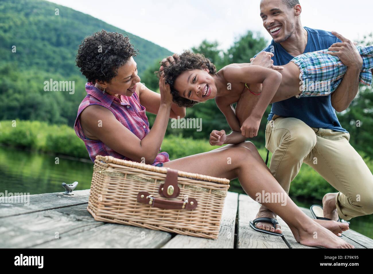 Une famille ayant un pique-nique d'été au bord d'un lac. Photo Stock