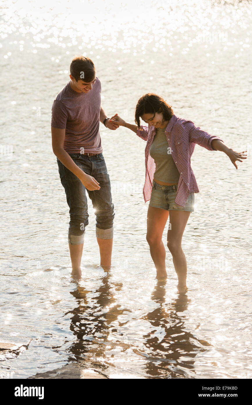 Un couple holding hands, pagayer en eau peu profonde au bord du lac. Photo Stock