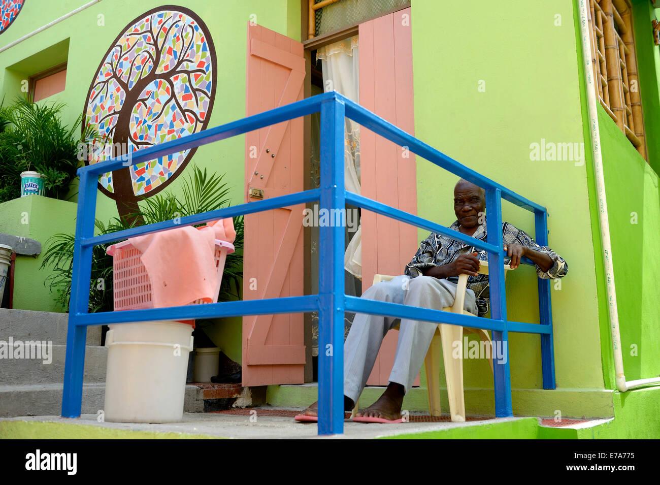 Vieil homme assis en face d'une maison qu'il construit avec l'appui d'un organisme de bienfaisance, Photo Stock