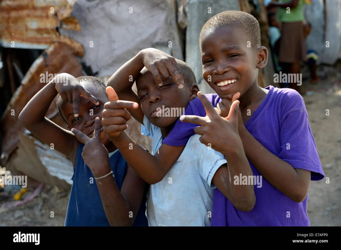 Trois garçons posant avec des gestes sauvages, Camp de réfugiés du séisme d'Icare, Fort National, Port-au-Prince, Banque D'Images