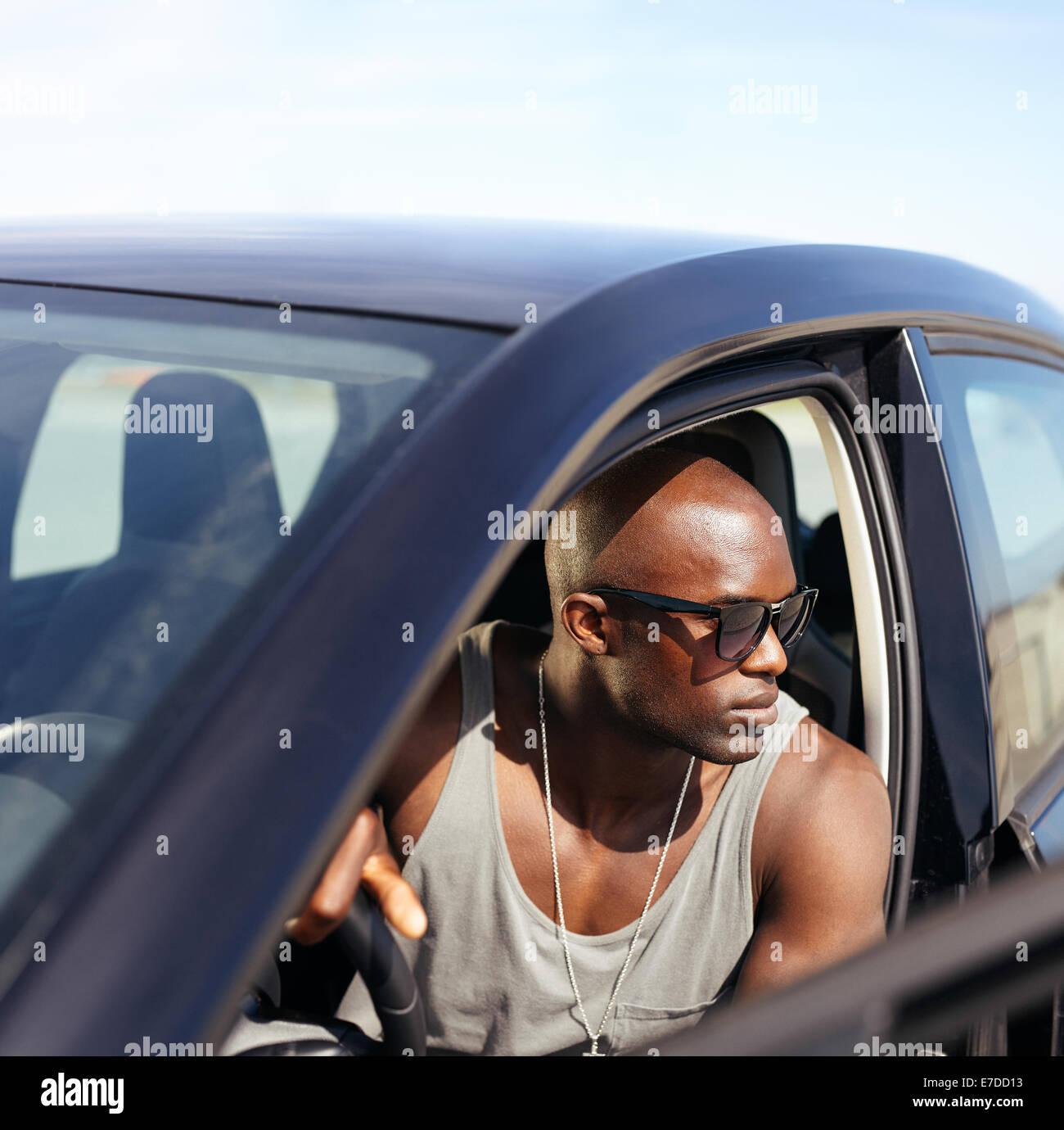 L'afro-américain guy assis dans sa voiture à la route. Jeune homme musclé au volant de sa voiture. Photo Stock