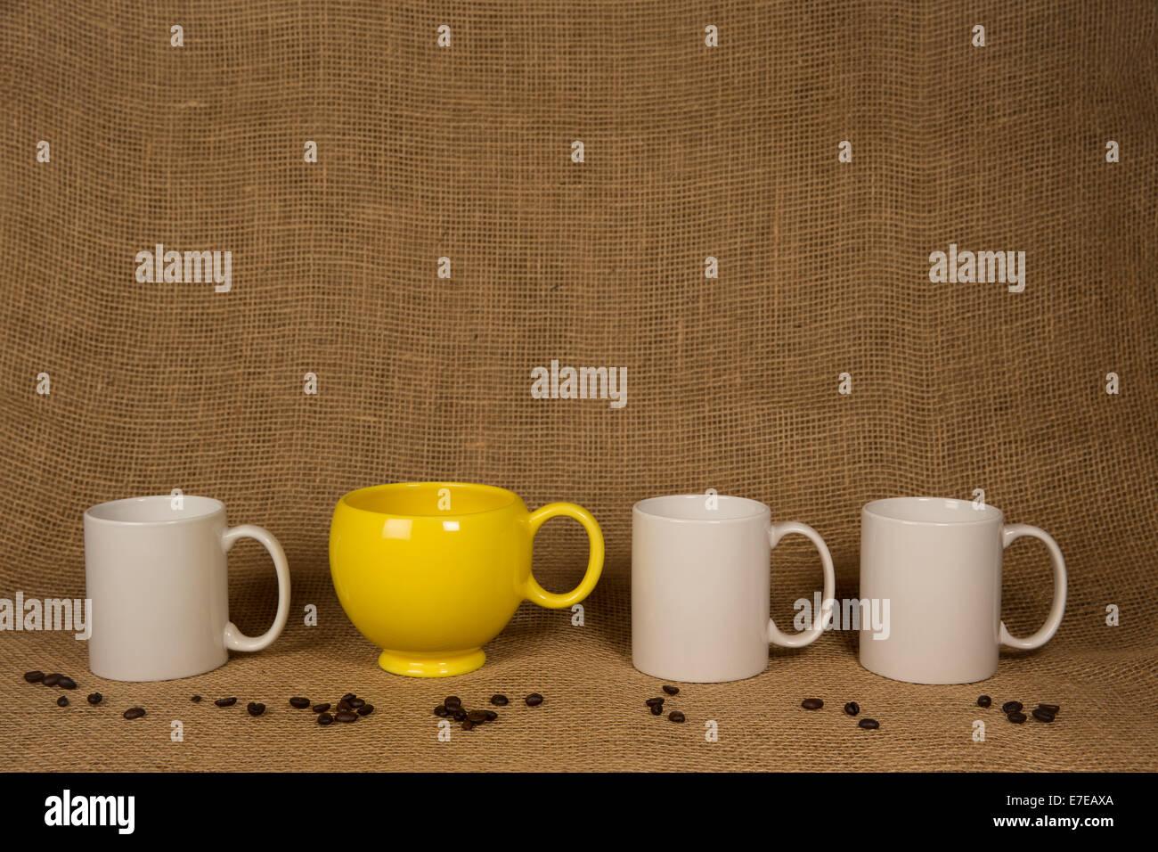 Fond tasse à café. Un mug jaune unique, trois blancs, les grains de café sur la toile de jute. Copie Photo Stock