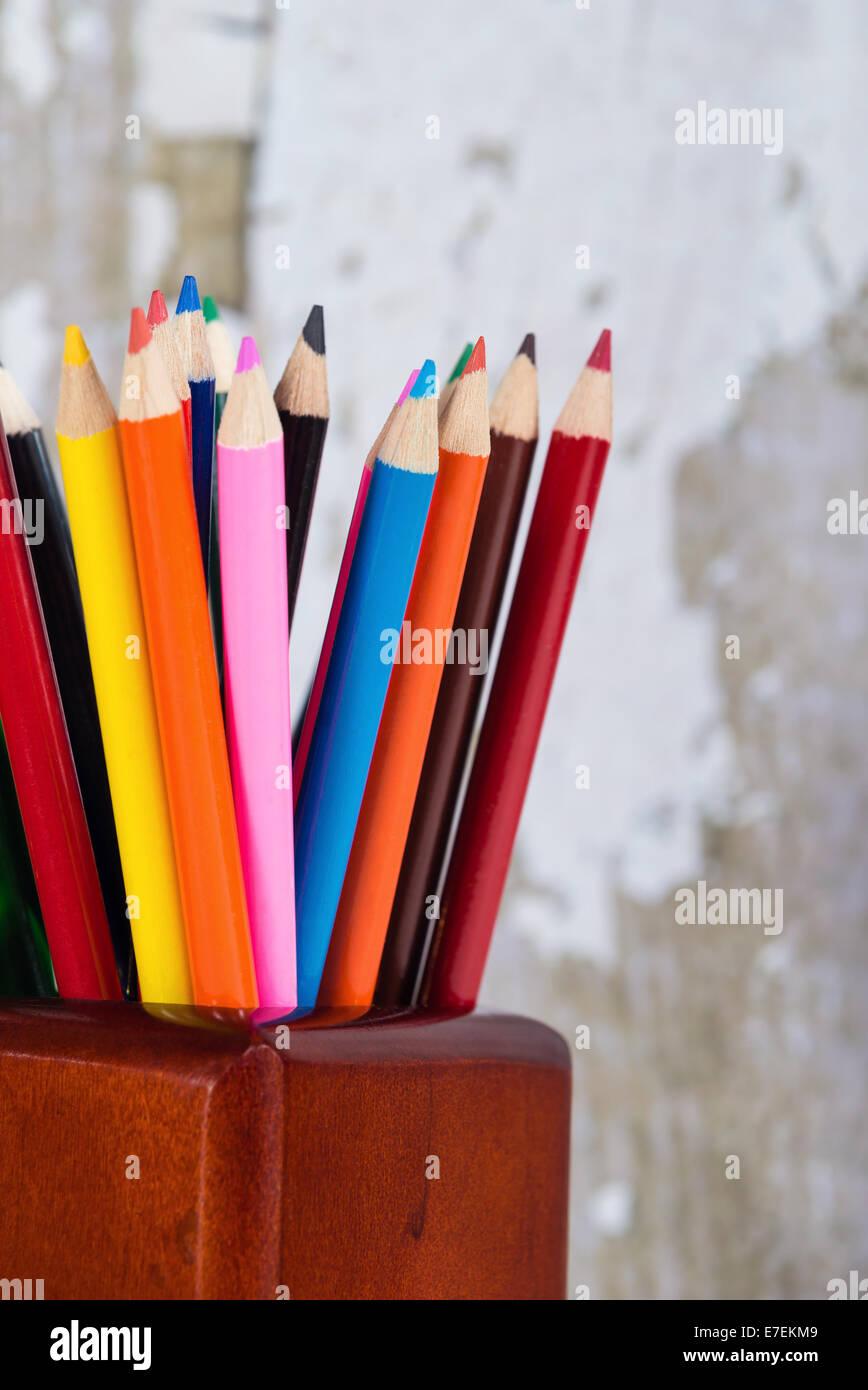 Groupe des crayons de couleur en porte-crayons contre l'arrière-plan gris Photo Stock