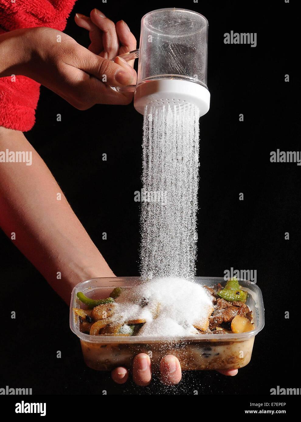 Une femme verse du sel sur un repas à emporter malsaine. Photo Stock