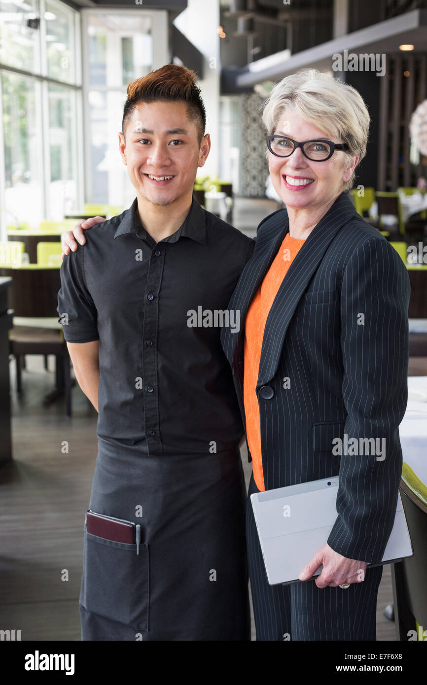 Businesswoman smiling in restaurant et de l'eau Banque D'Images