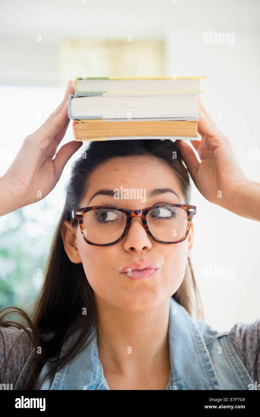 Woman balancing pile de livres sur la tête. Banque D'Images
