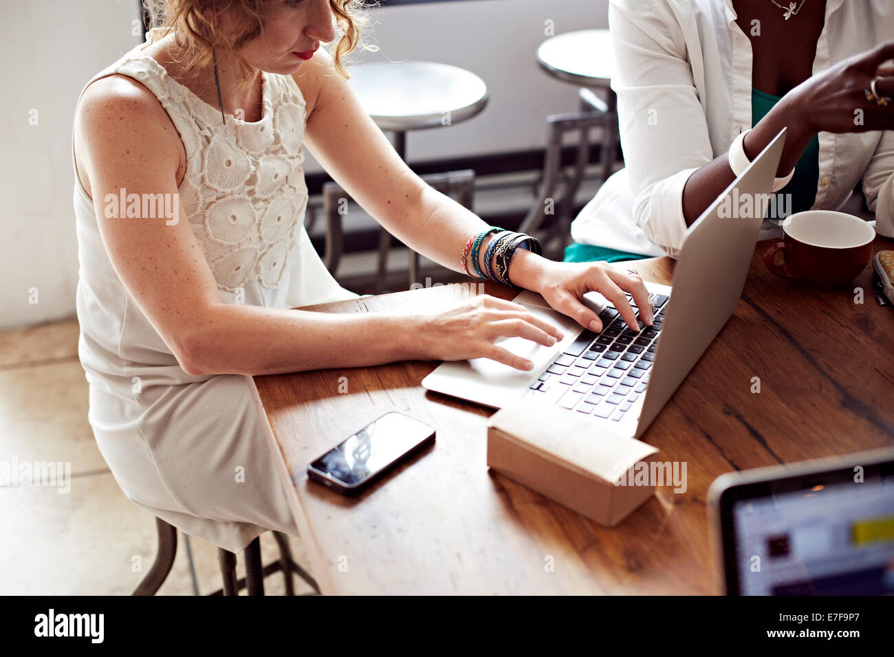 Woman using laptop in cafe Banque D'Images