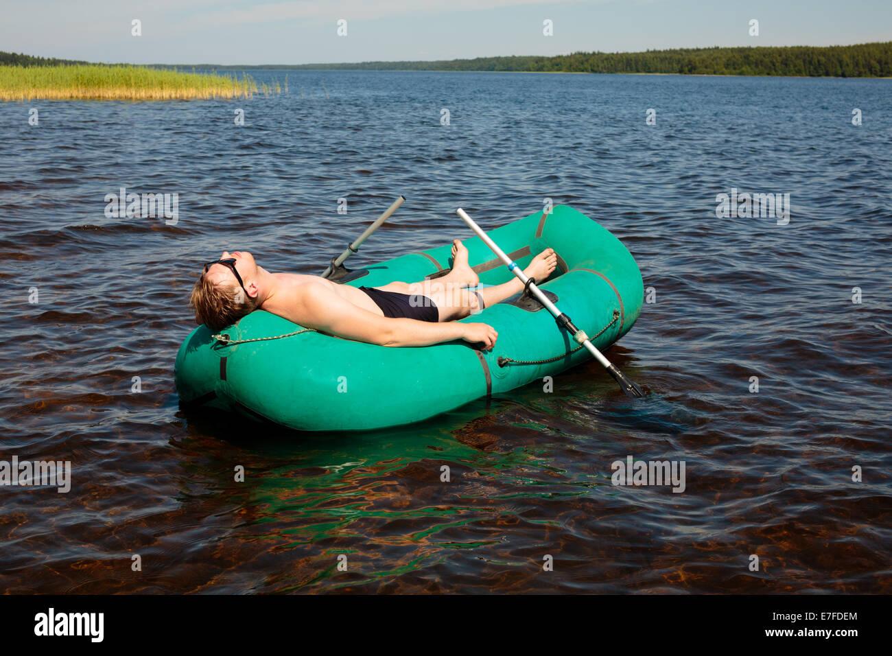 L'homme se reposant dans un bateau en caoutchouc Photo Stock