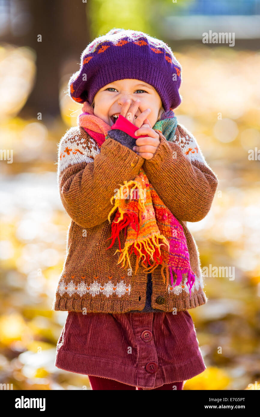 Happy little girl playing in the autumn park Photo Stock