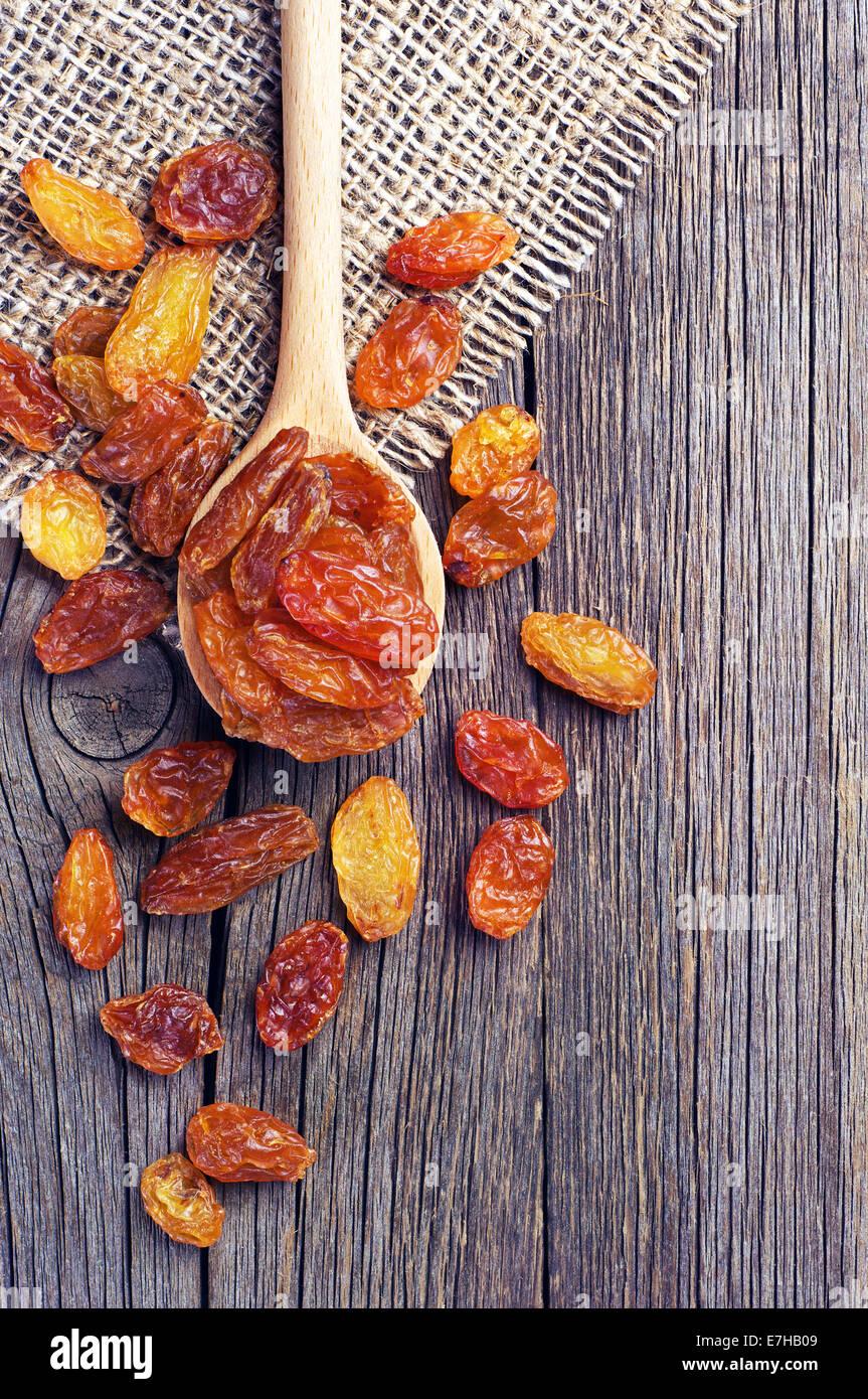 Les raisins secs dans une cuillère en bois sur fond de bois vintage Banque D'Images