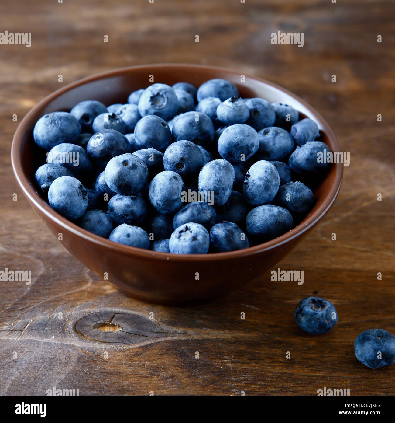 Bleuets frais dans un bol de planches de bois, des aliments sains Photo Stock