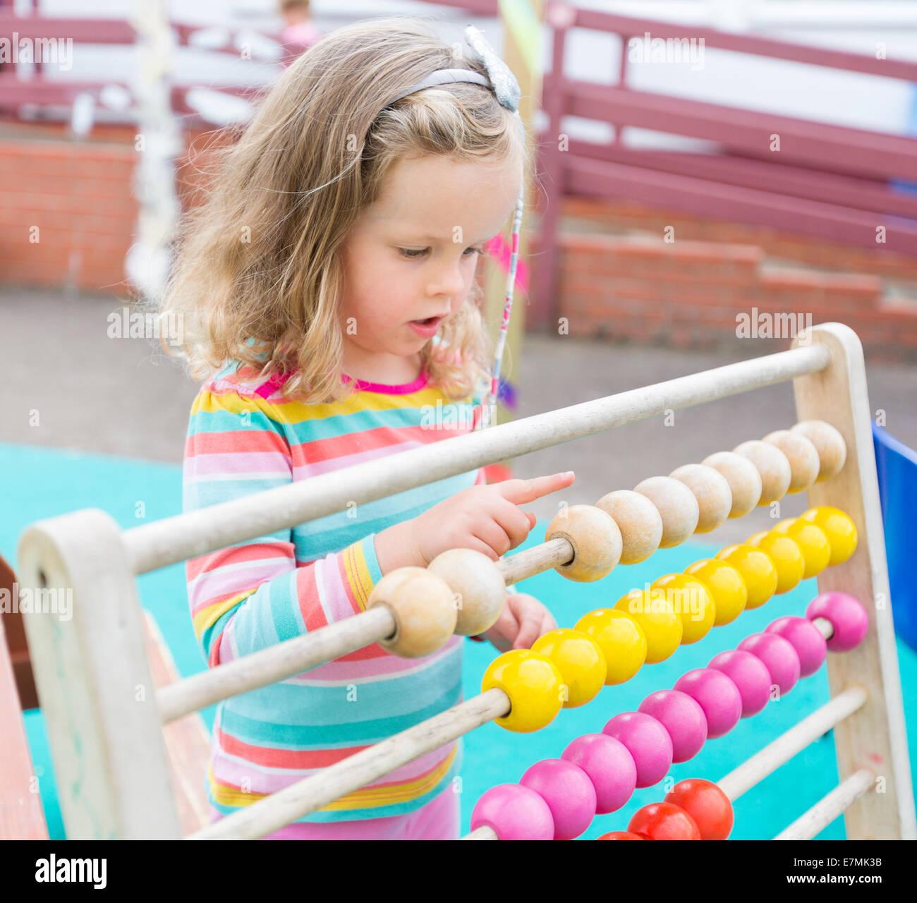 Une jeune fille compte sur un abaque à un UK nursery school Photo Stock