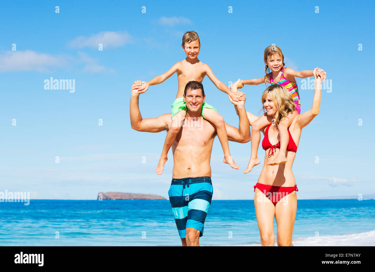 Famille heureuse de quatre s'amusant sur la plage Photo Stock