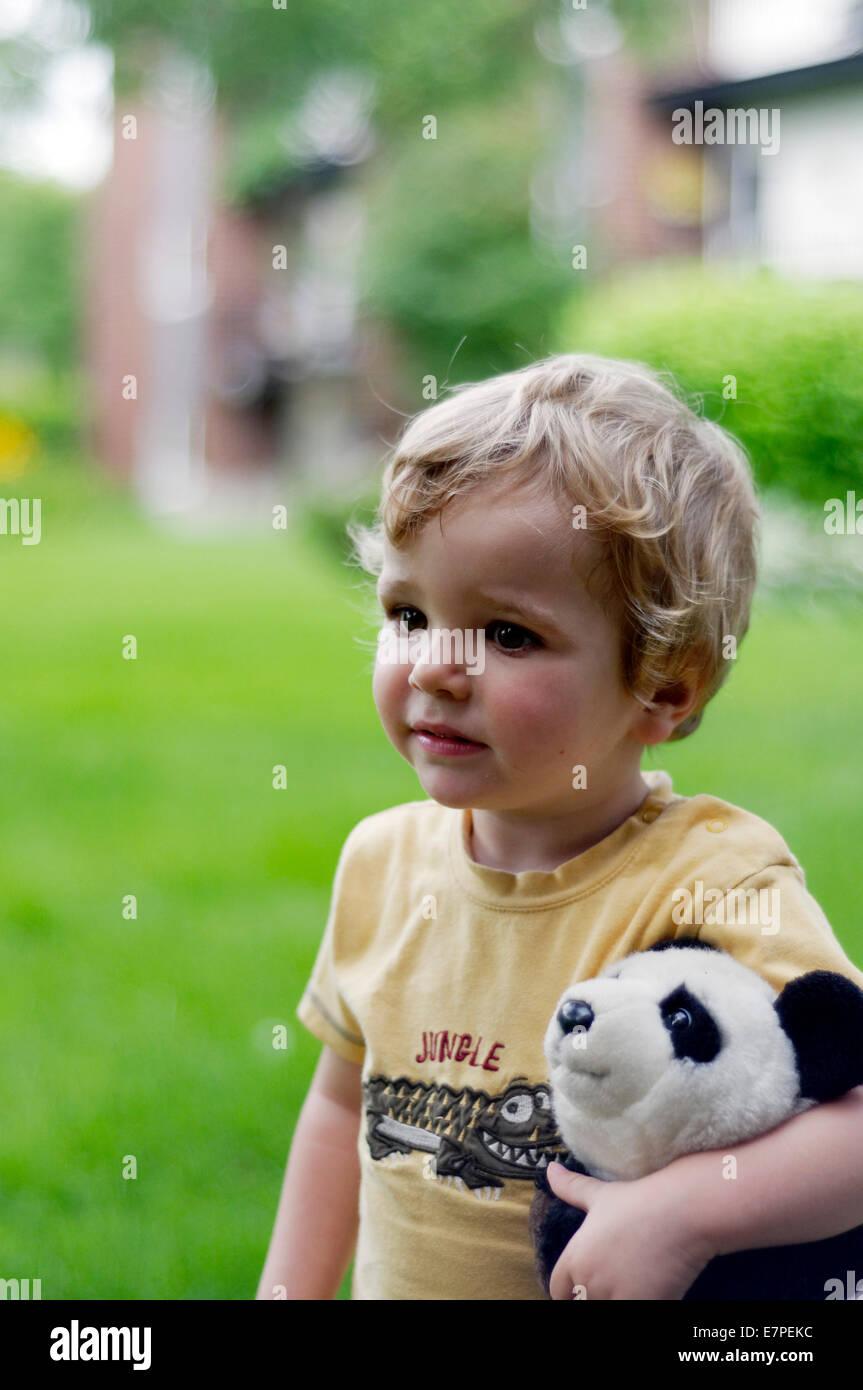 Portrait d'un petit garçon portant un panda jouet Photo Stock