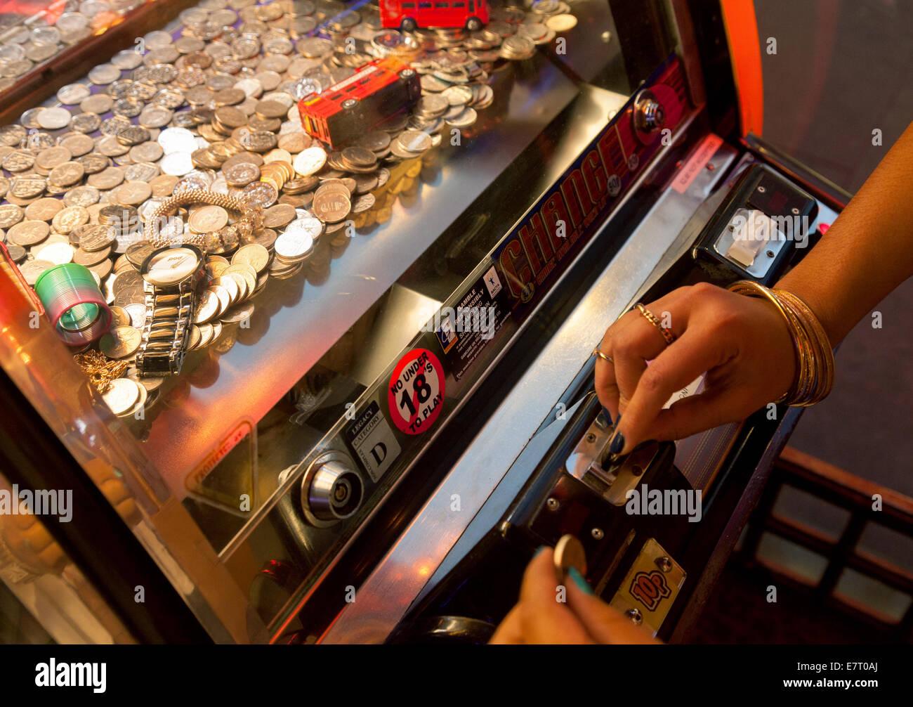 Les femmes mettre des pièces dans une machine de jeu dans une salle de jeux électroniques, Londres UK Photo Stock